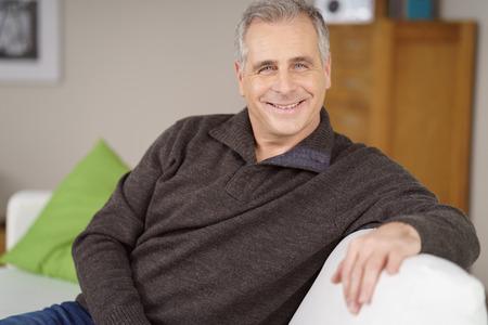 カリスマ的な幸せな魅力的な中年男晴れやかな笑みを浮かべてカメラを見て家でソファでリラックス 写真素材