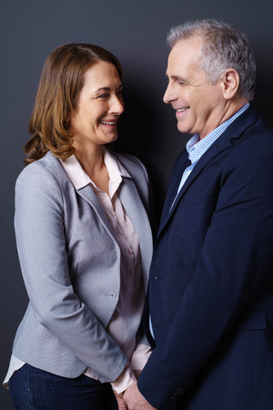 life partners: Business and life partners stand face to face and smile while resting against a dark blue background