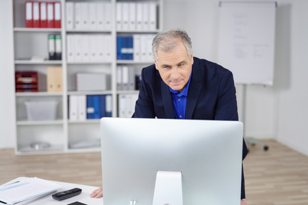 peering: Middle-aged businessman working at a computer standing peering down at a large desktop monitor with a serious expression