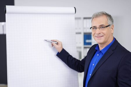 presenting: Confident business giving a presentation at the office standing in front of blank flip chart pointing with a pen while smiling at the camera