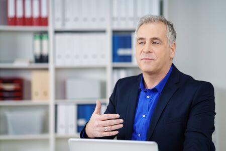 hombres maduros: El hombre de negocios hablando con un colega fuera de la pantalla haciendo un gesto con la mano mientras explica algo mientras está sentado en una computadora portátil