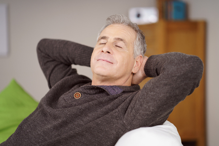 hands on head: Attractive middle-aged man relaxing at home reclining on a comfortable sofa with his hands behind his head and eyes closed in pleasure