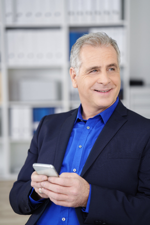 preoccupied: Pre-occupied handsome middle-aged businessman holding a mobile phone in his hands looking off to the right of the screen Stock Photo