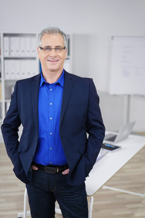 consultant: Successful confident stylish businessman wearing glasses standing with his hands in his suit pockets in the office grinning at the camera