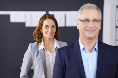 smiling businessman: Grinning business woman standing behind out of focus co-worker or employee in office with charts on blackboard