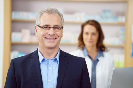 attended: Smiling business man at drug store counter being attended by female pharmacist besides medicine stocked shelves