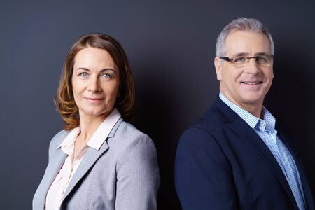 experienced: Business partners stand back to back against blue background and smile at camera while wearing open suit jackets