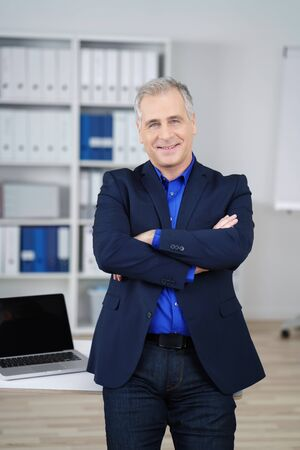 office manager: Confident middle-aged business executive standing in the office with folded arms smiling at the camera