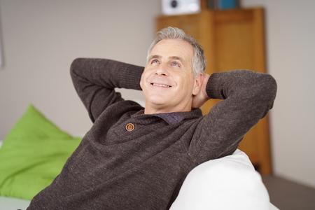 Felice uomo seduto a sognare ad occhi aperti a casa mentre si rilassa su un divano con le mani intrecciate dietro la sua testa guardando in aria con un sorriso raggiante Archivio Fotografico