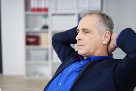 office manager: Worried businessman pondering on a problem sitting with his hands clasped behind his head staring ahead with a solemn contemplative expression