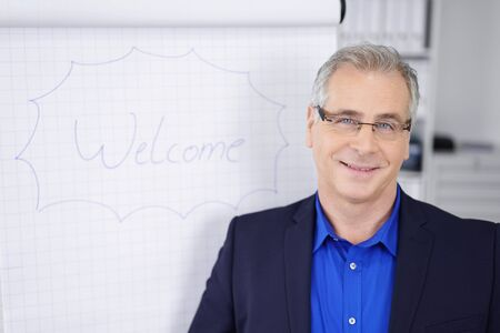 business attire teacher: Middle-aged businessman doing a presentation in the office standing alongside a flip chart with the word Welcome smiling at the camera