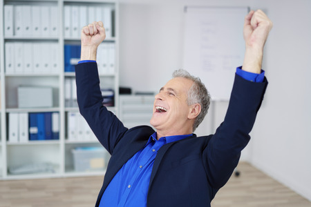 jubilate: Exultant businessman cheering and raising his fists in the air as he celebrates a victory or milestone