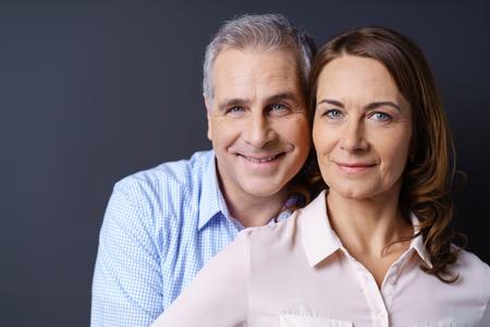 青色の背景で夫婦を笑顔とビジネス カジュアルな服を着てのクローズ アップ