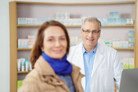 therapie: Friendly male pharmacist assisting a woman patient standing behind the counter in the pharmacy smiling at the camera
