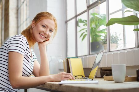 Online Business: Smiling happy young woman studying at home sitting at a work table with her notes and laptop looking at the camera with a friendly grin