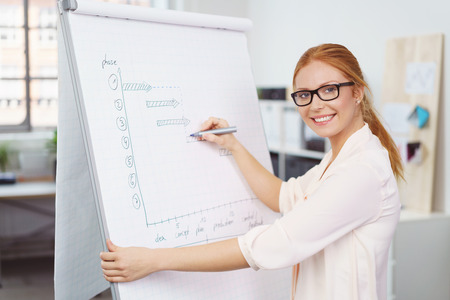 Attractive young businesswoman preparing a presentation writing notes on a flip chart in the office turning to smile at the camera