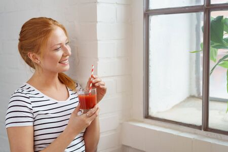 functional: Single happy young red haired woman holding carrot juice with red and white straw looking outside of window