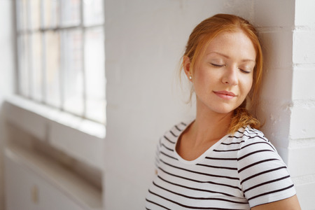 Red haired woman in striped shirt closes her eyes while resting against a white painted brick wall near window