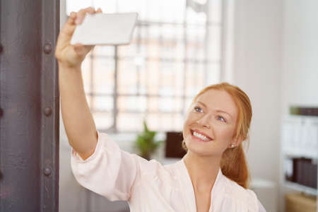 casual woman: Smiling young redhead woman posing for a selfie inside the office holding up her smartphone as she grins happily at the camera