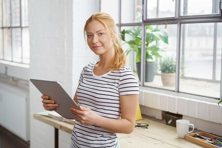 girl with laptop: Smiling happy young woman working on a tablet in a design studio standing at her desk in front of a window with plants looking at the camera Stock Photo