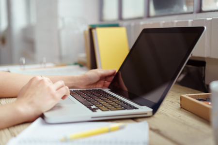 teleworker: Close up of worker hands typing on laptop with blank black screen over wooden desk with stack of books beside windows