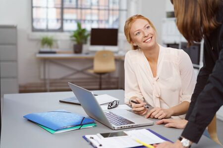 employees: Two businesswomen enjoying a friendly chat at the office with a manageress or supervisor leaning over a table talking to a smiling happy employee
