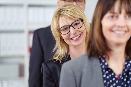 mujeres juntas: Tres personas de negocios sonriente de pie en una línea mientras se usan las chaquetas del juego cerca de estante con aglutinantes Foto de archivo