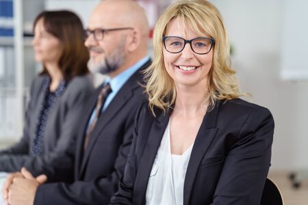 executive women: Blond business woman in suit jacket smiles at camera while seated next to others in a conference Stock Photo
