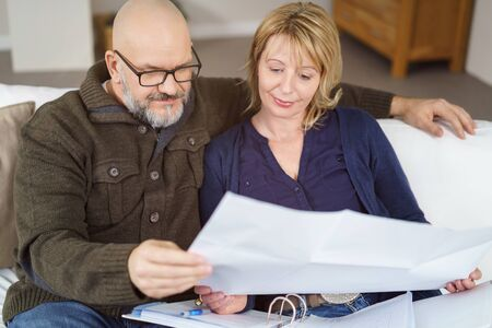 greying: Bald man with greying beard on couch with one arm around his wife looking through binder and unfolded paper
