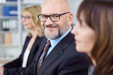 mujeres sentadas: Hombre calvo con gafas y traje de negocios sonríe a la cámara mientras se está sentado entre dos mujeres en una conferencia Foto de archivo