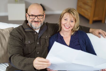 donna innamorata: Handsome bald man and his wife seated on couch and smiling at the camera while holding paperwork Archivio Fotografico