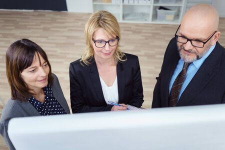 high angle view: High angle view down toward team of three mature male and female business people looking at chart during a meeting in office Stock Photo