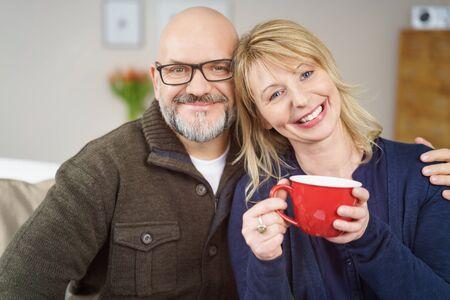hombre calvo: Hombre calvo con gafas sentado junto a la mujer que sostiene la taza de café roja en el sofá en su sala de estar Foto de archivo