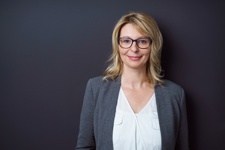 Single grinning mature business woman in eyeglasses in front of dark colored wall with copy space