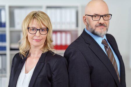 ragazze bionde: Due uomini d'affari seus in giacche e occhiali levano in piedi vicino a scaffale e spalla a spalla Archivio Fotografico