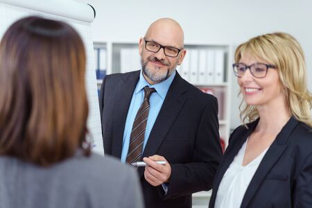 intrigued: Intrigued business man with eye glasses and suit conducts meeting and holds marker while standing near two women and white board