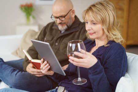 e book device: Middle-aged couple relaxing at home together with a glass of wine with the man reading a book and the woman a tablet