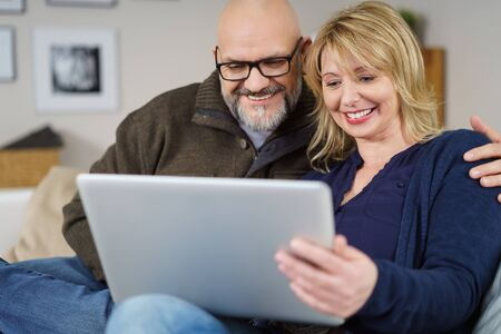 inside: Excited couple seated on couch in living room holding and reading their tablet near wall with framed photos
