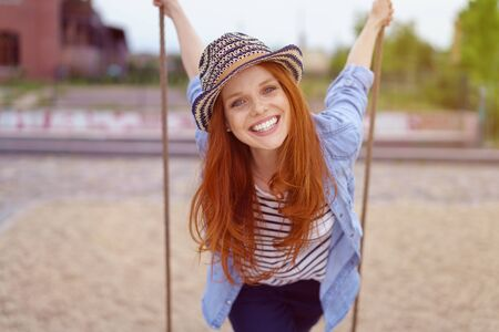 leaning forward: Vivacious pretty young redhead woman in a trendy outfit with a hat leaning forward on a swing in an urban park