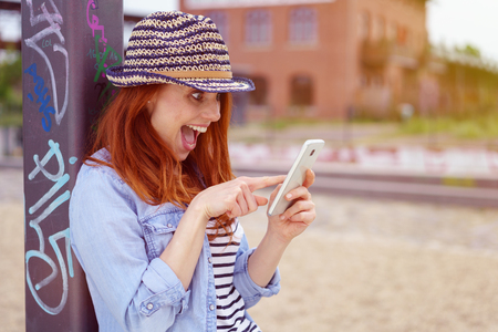 Excited young redhead woman in a trendy hat squealing in delight as she reads a text message on her mobile while leaning against a post in an urban square