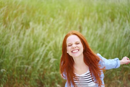 green eyes: Playful young redhead woman frolicking in a spring field dancing around with outstretched arms grinning at the camera, with copy space