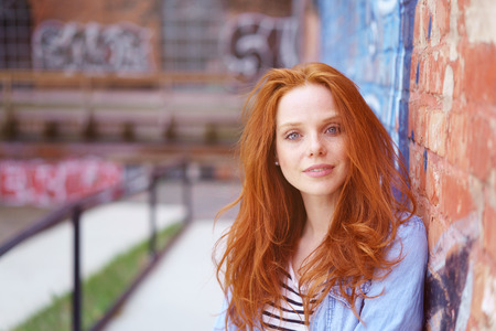 tousled: Attractive young woman with tousled red hair leaning against an exterior brick wall with graffiti looking at the camera with a quiet smile