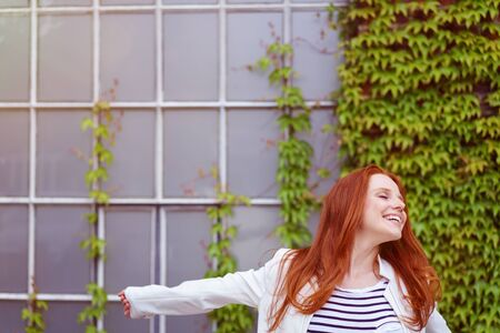 jaunty: Jaunty young redhead woman posing for the camera outside a creeper covered wall leaning to the side with a beaming smile