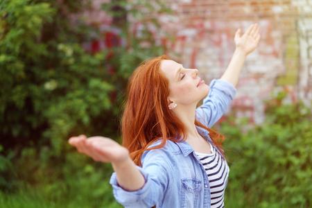 꽤 젊은여자가 그녀의 팔을 봄 정원에서 야외 서 자연의 평화를 즐기고 뻗은 눈과 기쁨의 미소로 폐쇄
