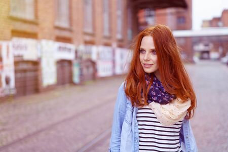 Smiling cute young woman in red hair and blue denim shirt standing among warehouse industrial buildings outdoors