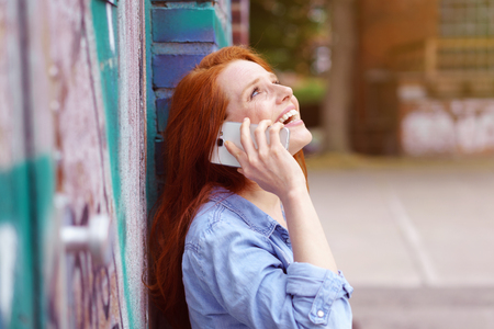 chats: Young woman laughing as she chats on a mobile phone while leaning against on old exterior brick wall, close up view