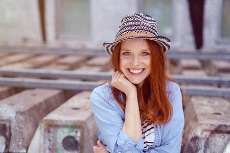 hand rails: Pretty woman with red hair, cute hat and blue denim shirt resting chin in hand with rails behind her Stock Photo