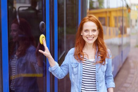 Smiling beautiful red haired young adult woman in blue denim and striped shirt pressing large yellow button on tram door Reklamní fotografie