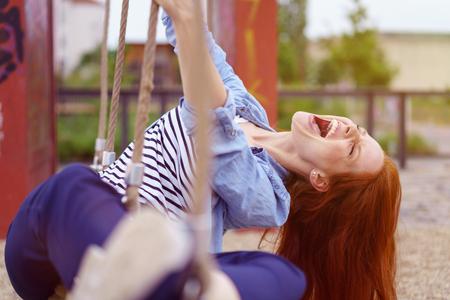 Carefree mujer pelirroja bastante joven que se divierte en un parque urbano que juega en un columpio de cuerda y disfrutando de una risa calurosa