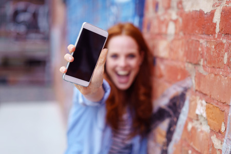 Excited young woman screaming and showing the blank screen of her mobile phone to the camera, focus to the phone Stockfoto